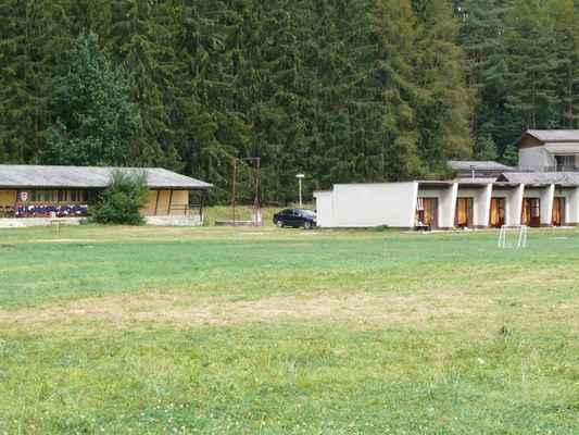 Ubytování a hřiště na louce - Vlevo dřevěná ubytovna, kde bydleli starší kluci, vpravo zděné bungalovy pro prcky